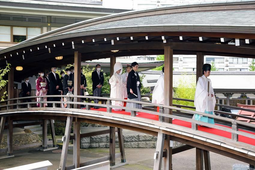 いよいよ挙式。神主様の先導でお太鼓橋を渡り神殿へ。